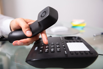 Compare business phone systems hand dialing phone.
