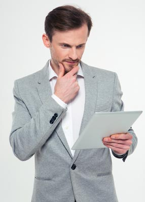 Business owner reading tablet about VoIP benefits.